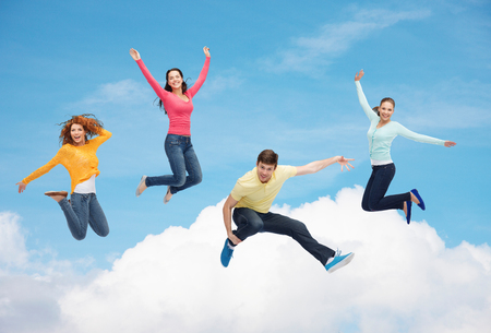 happiness, freedom, friendship, movement and people concept - group of smiling teenagers jumping in air over blue sky with white cloud background photo