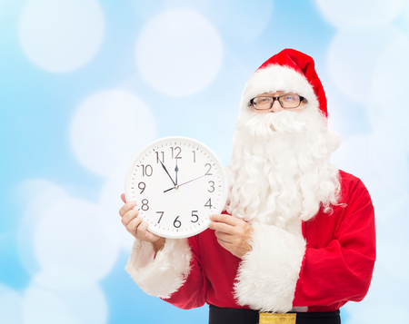 12 oclock: christmas, holidays and people concept - man in costume of santa claus with clock showing twelve over blue lights background Stock Photo