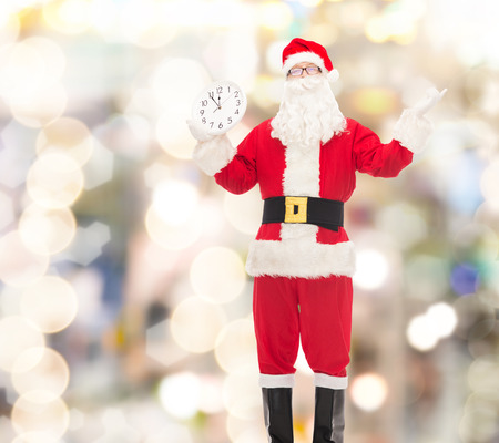 12 oclock: christmas, holidays and people concept - man in costume of santa claus with clock showing twelve over lights background Stock Photo