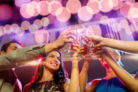 vip: party, holidays, celebration, nightlife and people concept - smiling friends with glasses of champagne in club