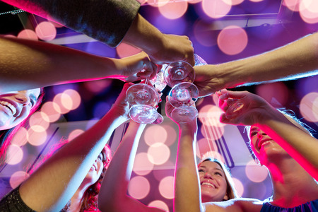 champagne glasses: party, holidays, celebration, nightlife and people concept - smiling friends with glasses of champagne in club