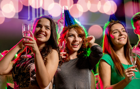 party, holidays, celebration, nightlife and people concept - smiling friends with glasses of champagne in club photo