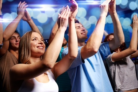 people looking up: party, holidays, celebration, nightlife and people concept - smiling friends applauding at concert in club