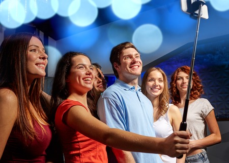 party, technology, nightlife and people concept - smiling friends with smartphone and monopod taking selfie in club