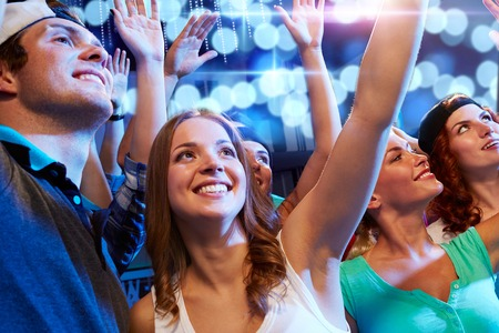 clubbers: party, holidays, celebration, nightlife and people concept - smiling friends waving hands at concert in club