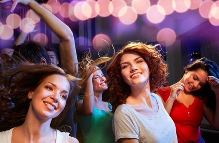 night out: party, holidays, celebration, nightlife and people concept - smiling friends dancing at concert in club