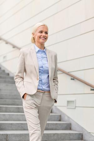 bajando escaleras: negocio, la gente y el concepto de la educaci�n - joven empresaria sonriente caminando por las escaleras al aire libre Foto de archivo
