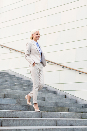 down town: business, people and education concept - young smiling businesswoman walking down stairs outdoors Stock Photo