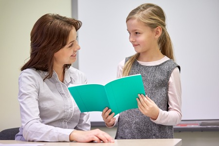 girl studying: education, elementary school, learning, examination and people concept - school girl with notebook and teacher in classroom Stock Photo