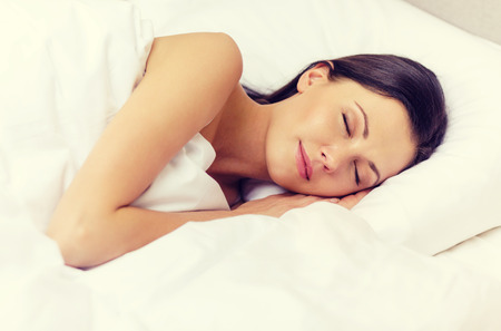 CALM WOMAN: hotel, travel and happiness concept - beautiful woman sleeping in bed Stock Photo