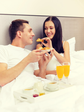 breakfast in bed: hotel, travel, relationships and happiness concept - smiling couple having breakfast in bed in hotel room Stock Photo