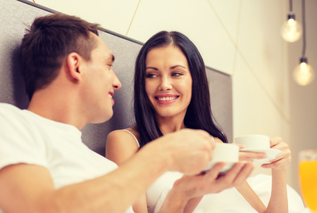 hotel, travel, relationships and happiness concept - smiling couple having breakfast in bed in hotel room Stock Photo