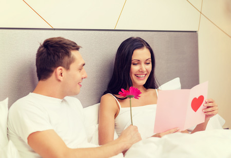 hotel, travel, relationships, holidays and happiness concept - smiling couple in bed with postcard and pink flower photo