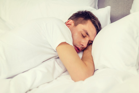 hotel bed: hotel, travel and happiness concept - handsome man sleeping in bed Stock Photo