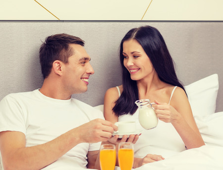 romance bed: hotel, travel, relationships and happiness concept - smiling couple having breakfast in bed in hotel room Stock Photo