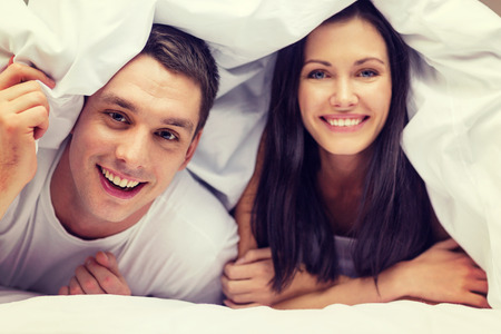romance bed: hotel, travel, relationships, and happiness concept - happy couple in bed Stock Photo