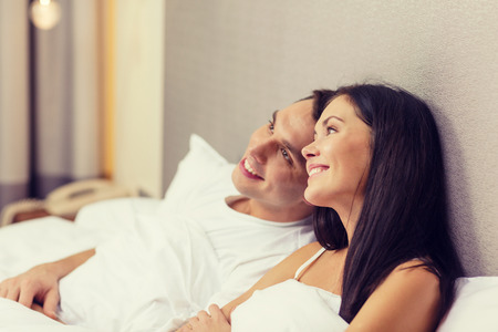 romance bed: hotel, travel, relationships, and happiness concept - happy couple dreaming in bed Stock Photo
