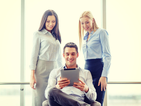 business and office concept - smiling business team working with tablet pc in office photo