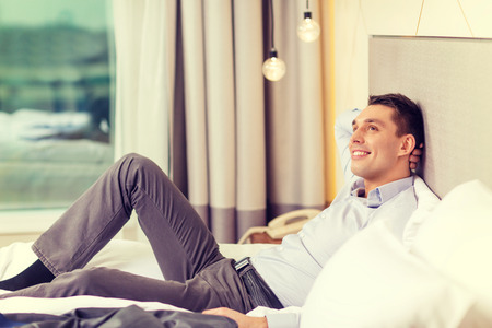lay: business, technology, internet and hotel concept - happy businesswoman lying in bed in hotel room Stock Photo