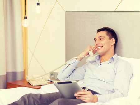 business, technology, internet and hotel concept - happy businessman with phone and tablet pc computer lying in hotel in bed photo