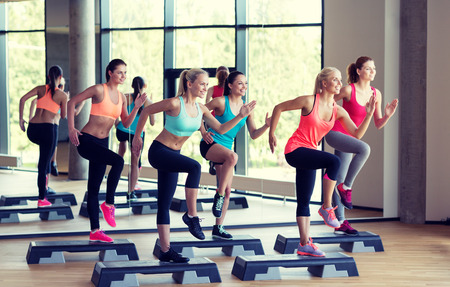 fitness, sport, training, gym and lifestyle concept - group of women working out with steppers in gym Stockfoto