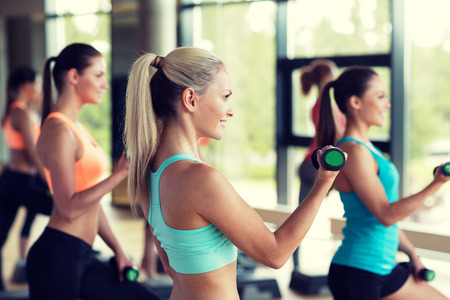 step fitness: fitness, sport, training, gym and lifestyle concept - group of women working out with dumbbells and steppers in gym