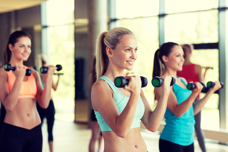 group training: fitness, sport, training, gym and lifestyle concept - group of women with dumbbells in gym
