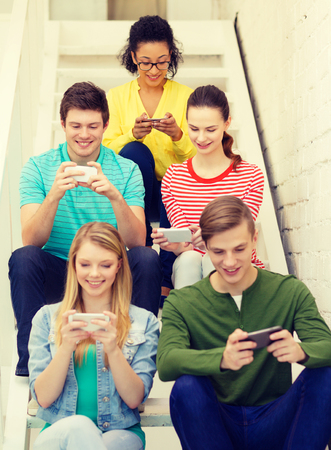 gamers: education, school and technology concept - smiling students with smartphone texting at school Stock Photo