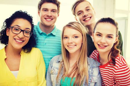 교육 및 행복 개념 - 집 또는 학교에서 젊은 웃는 사람들의 그룹 스톡 콘텐츠