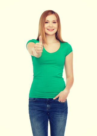 teenage girl happy: happiness, gesture and people concept - smiling teenage girl in casual clothes showing thumbs up Stock Photo