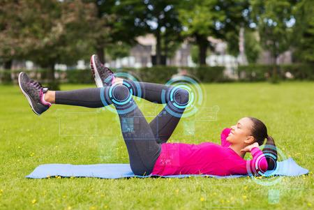 フィットネス、スポーツ、トレーニング、公園やライフ スタイル コンセプト - マット屋外で演習を行って女性を笑顔