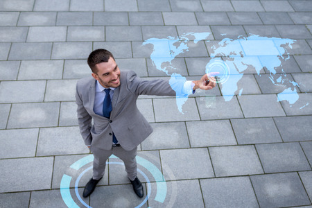 top of the world: global business, development, technology and people and concept - young smiling businessman pointing finger to world map projection outdoors from top