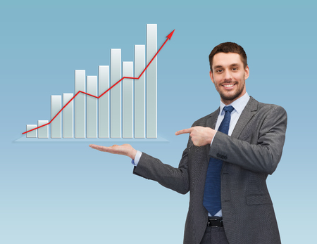 business, success, economics, and people concept - smiling young businessman pointing finger and showing growth chart on palm of his hand over blue background photo