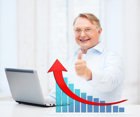 technology, oldness, people, success and business concept - old man in eyeglasses with laptop computer showing thumbs up over office background and growth chart Stock Photo