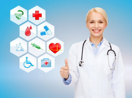 healthcare, medicine, people, gesture and symbols concept - smiling young female doctor or nurse with stethoscope showing thumbs up over medical icons and blue background photo