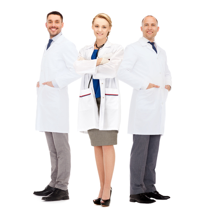 white coats: healthcare, profession and medicine concept - group of smiling doctors in white coats over white background