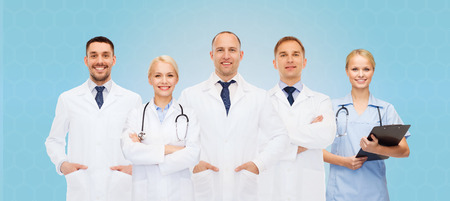 healthcare, people and medicine concept - group of doctors with stethoscopes and clipboard over blue background photo