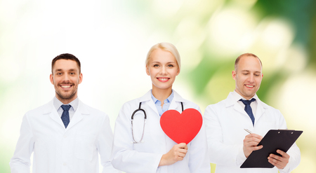 medics: medicine, profession, teamwork and healthcare concept - group of smiling medics or doctors holding red paper heart shape, clipboard and stethoscopes over green background