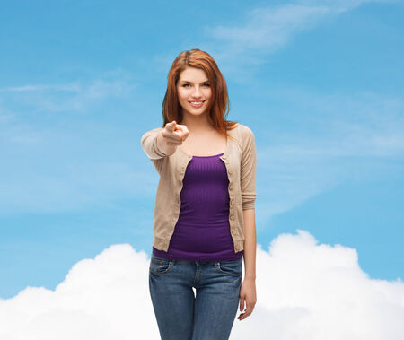 woman pointing up: future, dream, gesture and people concept - smiling teenage girl in casual clothes pointing finger on you over blue sky and cloud background