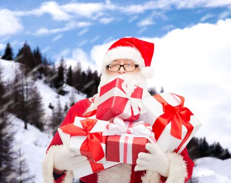 christmas, holidays and people concept - man in costume of santa claus with gift boxes over snowy mountains background photo