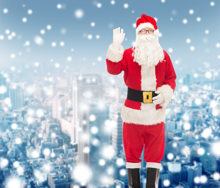 christmas, holidays, gesture and people concept - man in costume of santa claus waving hand over snowy city background photo
