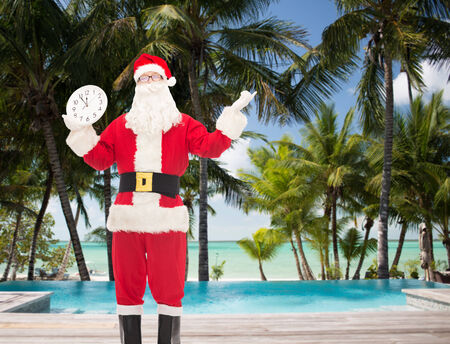 12 oclock: christmas, holidays, travel and people concept - man in costume of santa claus with clock showing twelve over tropical beach and swimming pool background