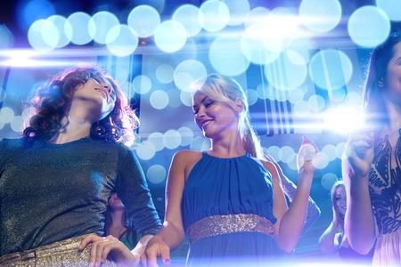 chicas bailando: fiesta, d�as de fiesta, celebraci�n, vida nocturna y Concepto - sonriente amigos bailando en el club Foto de archivo