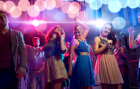 high society: party, holidays, celebration, nightlife and people concept - smiling friends dancing in club