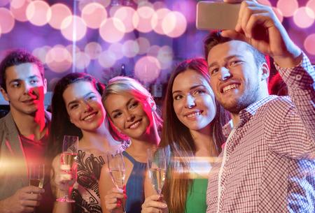 グラス シャンパンとクラブで selfie を取ってスマート フォンの友達に笑顔 - パーティー、休日、技術、ナイトライフ、人々 の概念