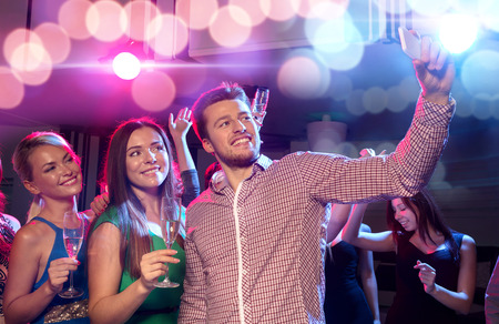 party, holidays, technology, nightlife and people concept - smiling friends with glasses of champagne and smartphone taking selfie in club photo