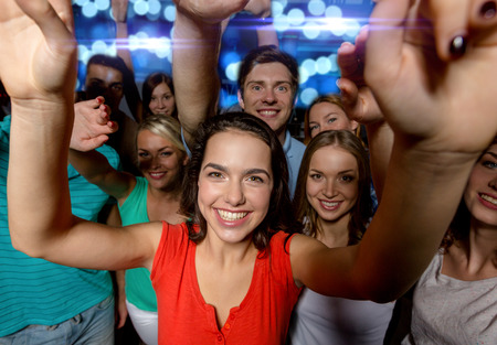 people having fun: party, holidays, celebration, friends and people concept - smiling friends dancing and waving hands in club Stock Photo