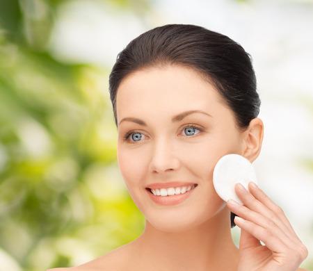 pulizia viso: bellezza, le persone e il concetto di salute - sorridente bella donna di pulizia pelle del viso con un batuffolo di cotone su sfondo verde