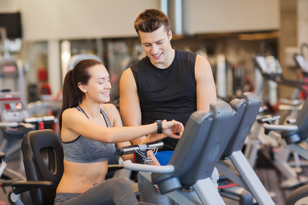 heart monitor: sport, fitness, lifestyle, technology and people concept - happy woman with trainer working out on exercise bike in gym Stock Photo