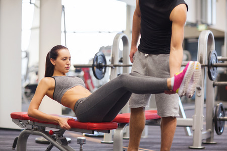 abdominal muscles: fitness, sport, training, teamwork and lifestyle concept - woman with personal trainer doing abdominal exercise in gym Stock Photo